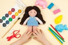 A criança senta-se na tabela com objetos para a faculdade criadora, o desenho e os passatempos, posses uma boneca feita crochê na foto de stock