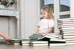 A criança senta-se no assoalho, rearranjando livros Foto de Stock Royalty Free