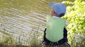 A criança senta-se no banco de rio e olha-se no rio vídeos de arquivo