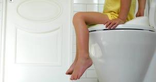 A criança senta-se no toalete video estoque