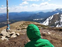 A criança senta-se sobre a montanha a mais alta em Ucrânia imagens de stock