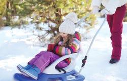Criança sledding da mãe no inverno Fotografia de Stock Royalty Free
