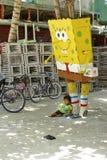 Criança sob uma estátua dos desenhos animados Imagem de Stock
