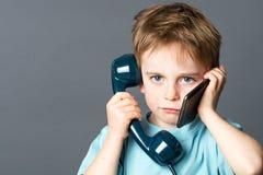Criança sobrecarregado que comunica-se em telefones novos e velhos Foto de Stock Royalty Free