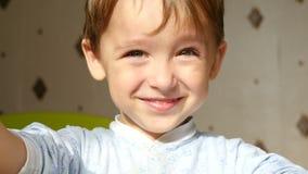 A criança sorri e pisc o close-up As emoções positivas reais de um menino dos anos de idade 3 no movimento lento vídeos de arquivo