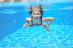 A criança subaquática ativa feliz nada na associação Fotos de Stock