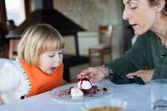 Criança surpreendida da cara que come o bolo com mãe Imagem de Stock