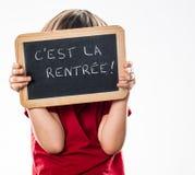 Criança tímida anônima oneself de proteção atrás da ardósia francesa da escrita Fotografia de Stock