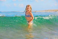 A criança tem um divertimento em quebrar ondas da praia fotos de stock