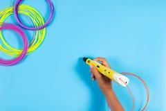 A criança tira com a pena 3d Criança que guarda a pena 3d com filamento plástico Foto de Stock Royalty Free