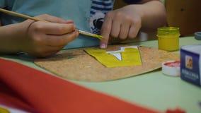 A criança tira cores brilhantes no papel A pintura na tabela As mãos da criança grandes Pouco artistDevelopment de video estoque