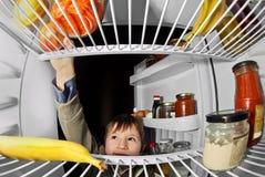 A criança toma o alimento do refrigerador Foto de Stock Royalty Free