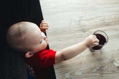 A criança toma uma bebida Fotografia de Stock Royalty Free