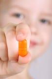A criança toma vitaminas Fotografia de Stock Royalty Free