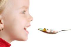 A criança toma vitaminas pela colher Fotografia de Stock