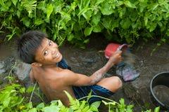 A criança trava peixes pequenos em uma vala Fotografia de Stock Royalty Free