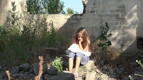 Criança triste abandonada nas ruínas, menina dispersa infeliz, criança pobre deprimida, sem abrigo