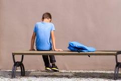 Criança triste, cansado que senta-se apenas no banco fora imagens de stock royalty free