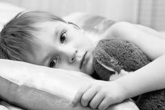 Criança triste com um urso de peluche Fotografia de Stock