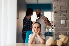 Criança triste durante a discussão dos pais fotos de stock royalty free