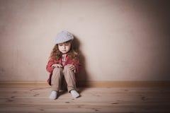 Criança triste que senta-se no assoalho imagens de stock