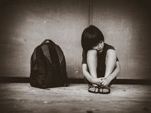 Criança triste que senta-se no assoalho com pai de espera do saco de escola fotos de stock