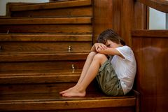 Criança triste, sentando-se em uma escadaria em uma casa grande, conceito para bu fotografia de stock royalty free