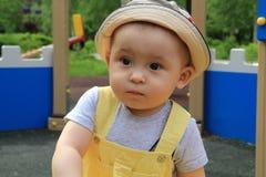 A criança, um rapaz pequeno anda no campo de jogos Fotos de Stock