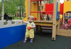 A criança, um rapaz pequeno anda no campo de jogos Imagens de Stock Royalty Free