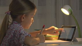 A criança usa a tabuleta estudando, menina que escreve trabalhos de casa no uso do Internet da noite fotografia de stock
