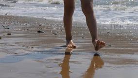 A criança vai ao longo da ressaca Os pés das crianças no fundo das ondas a água do mar lava afastado a pegada vídeos de arquivo