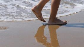 A criança vai ao longo da ressaca Os pés das crianças no fundo das ondas a água do mar lava afastado a pegada video estoque