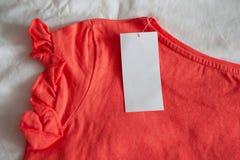 Criança vermelha cor-de-rosa nova ou t-shirt das mulheres com a etiqueta no fundo branco Compra do conceito, vendas do verão, des imagens de stock