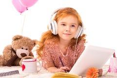 criança vermelha do cabelo que encontra-se no tapete e na música de escuta Fotografia de Stock Royalty Free