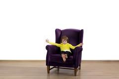 Criança vermelha feliz do cabelo que senta-se na poltrona roxa Imagens de Stock Royalty Free