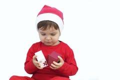 Criança vestida como Papai Noel com um presente Imagem de Stock
