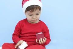 Criança vestida como Papai Noel com um presente Imagens de Stock Royalty Free