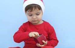 Criança vestida como Papai Noel com um presente Fotografia de Stock