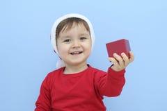 Criança vestida como Papai Noel com um presente Foto de Stock Royalty Free