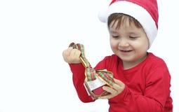 Criança vestida como Papai Noel com um presente Foto de Stock