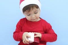 Criança vestida como Papai Noel com um presente Imagem de Stock Royalty Free