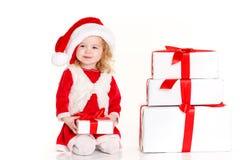 Criança vestida como Santa com um presente de Natal Foto de Stock