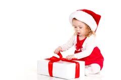 Criança vestida como Santa com um presente de Natal Fotografia de Stock