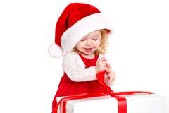 Criança vestida como Santa com um presente de Natal Fotografia de Stock Royalty Free