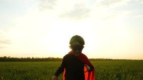 A criança, vestida como um super-herói em um casaco vermelho, corridas através da grama verde contra o por do sol, exulta e sorri vídeos de arquivo