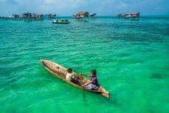 Crianças aciganadas do mar em sua sampana com sua casa em pernas de pau no fotografia de stock