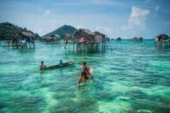 Crianças aciganadas do mar em sua sampana com sua casa em pernas de pau no imagem de stock