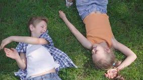 Crianças adoráveis bonitos do divertimento do retrato dois que encontram-se na grama no parque que sorri entre si Menina engraçad vídeos de arquivo