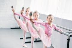 crianças adoráveis nas saias cor-de-rosa do tutu que praticam o bailado e que olham a câmera fotografia de stock royalty free