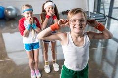 Crianças adoráveis no sportswear que engana ao redor no estúdio da aptidão fotografia de stock